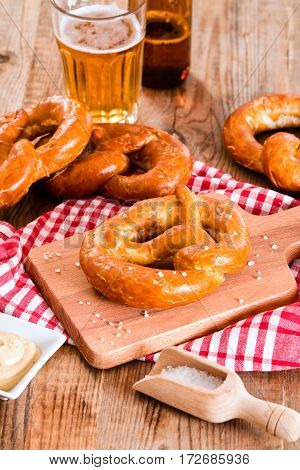 Bavarian pretzels with mustard and beer on cutting board.