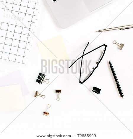 White office desk frame with paper blank and supplies. Laptop notebook pen clips glasses and office supplies on white background. Flat lay top view mockup.