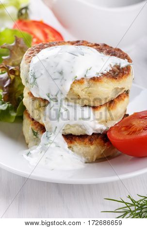 Vegetable cutlets from zucchini herbs and feta cheese with yogurt sauce.