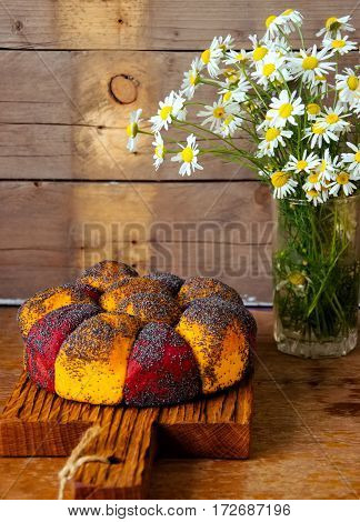 Carrot and beetroot bread with poppy seeds on a wooden board