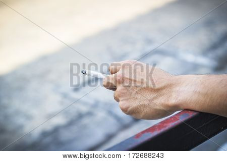 Man hand holding a cigarette smoking a cigarette with copy space.