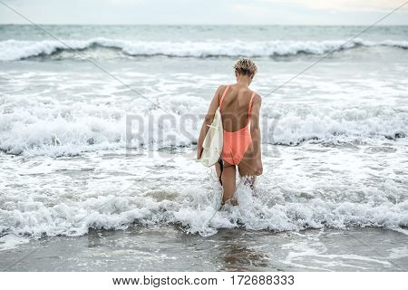 Athletic blonde girl with short hairstyle stands backsides in the waves on the beach on the background of the sea and the cloudy sky. She wears orange swimsuit with sunglasses and holds the surfboard.