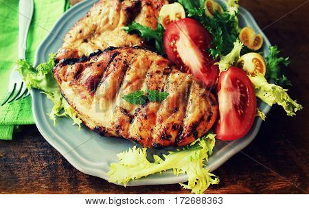Grilled chicken breast on wooden background .