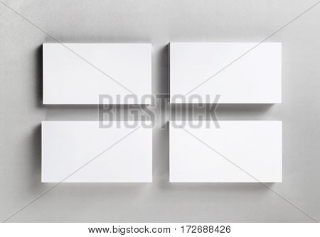 Four blank piles business cards on paper background. Template for ID. Business mockup. Blank objects for placing your design. Mock up for branding identity. Top view.