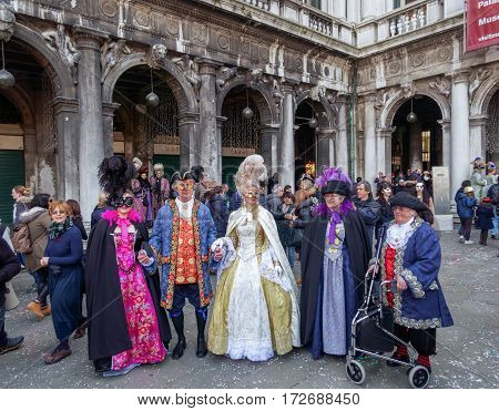 Venice, Italy - February 19 2017: Carnival mask and costume poses. Masked persons in traditional costume pose at PIazza San Marco during the Venice 2017 Carnival.