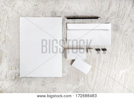 Photo of blank stationery set on light wooden table background. Corporate identity template. Branding mockup. Sheets of paper letterhead business cards envelope and pencil.