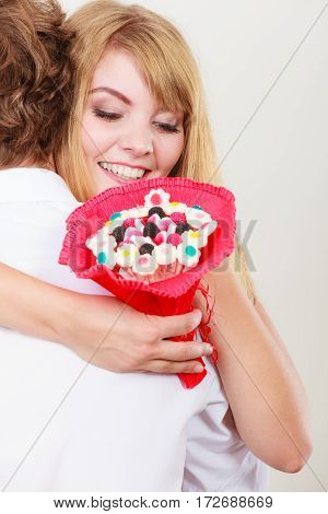 Loving couple with candy bunch bouquet flowers hugging. Pretty woman thanking man for present gift. Love concept.