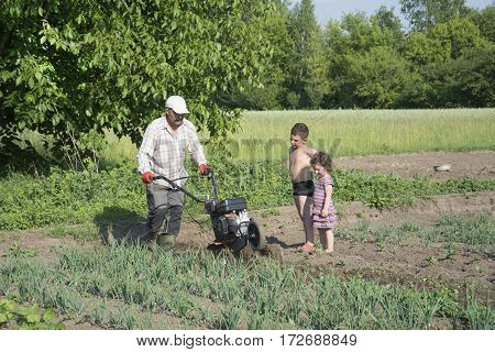 Spring bright sunny day in the garden man plowing land motor-block small son and daughter pomagajut him.