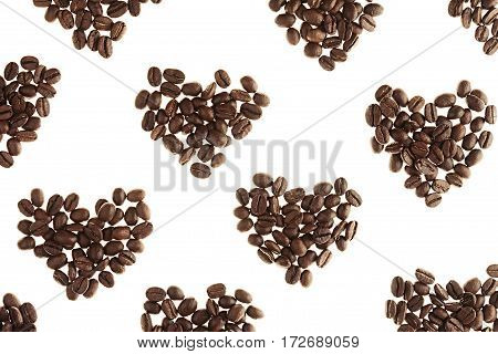 Heart pattern of heap roasted coffee beans isolated on white background.