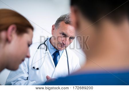 Thoughtful doctor standing with surgeons in corridor at hospital