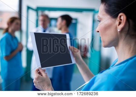 Surgeon examining a report in hospital