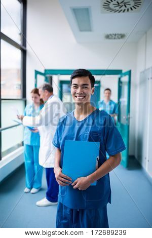 Smiling male surgeon holding a clipboard in corridor at hospital