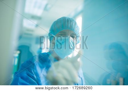 Doctor looking through a glass window in hospital