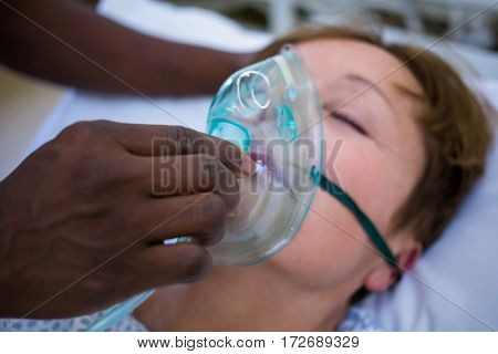 Nurse placing an oxygen mask on the face of a patient in hospital