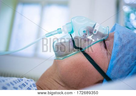 Patient wearing oxygen mask lying on bed in hospital
