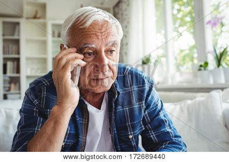 Tensed senior man talking on mobile phone at home