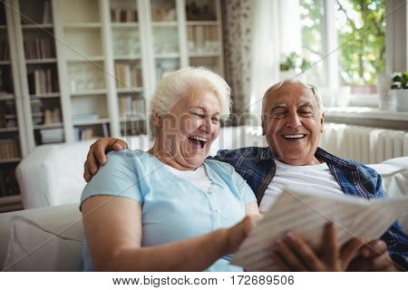 Senior couple looking at a photo album in home