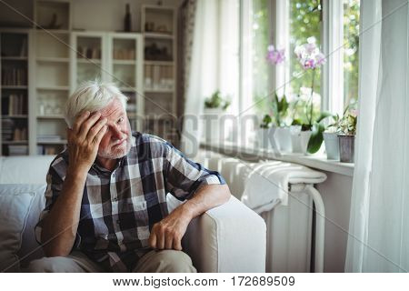 Tensed senior man sitting on sofa at home