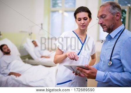 Doctor and nurse discussing over digital tablet in ward at hospital