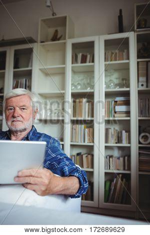 Portrait of senior man sitting on sofa and using digital tablet in living room