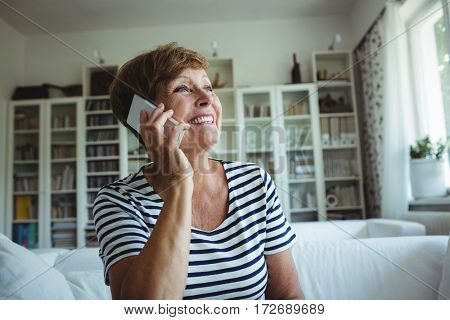 Senior woman talking on mobile phone in living room at home