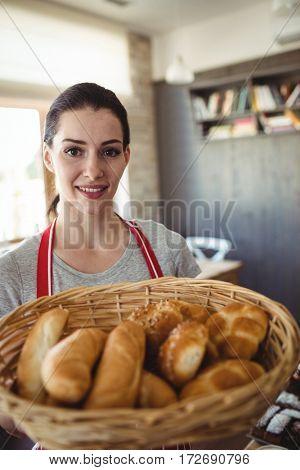 Portrait of female baker holding a basket of bread loafs in bakery shop