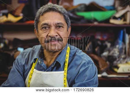 Portrait of smiling shoemaker standing in workshop
