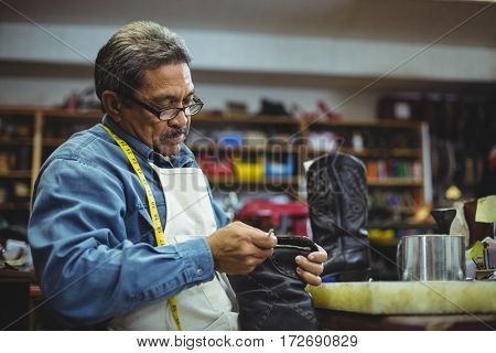 Shoemaker applying glue on shoe in workshop