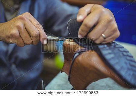 Shoemaker repairing a shoe sole in workshop