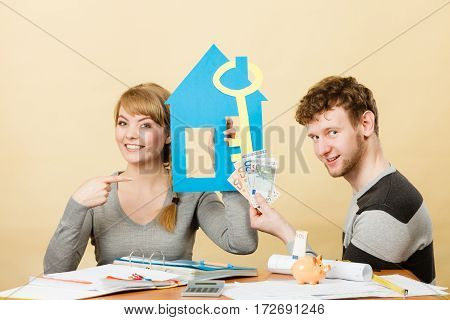 Purchase and construction investment. Just married lovely couple with model of their new home house. Woman and man with key to flat apartment and cash money.