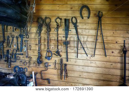 collection of vintage rustic tools on wooden wall