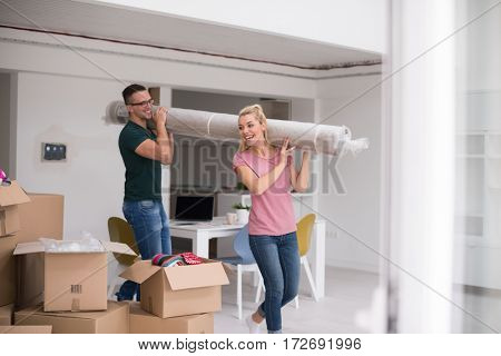 Young couple carrying a carpet moving in to new home together. Home, people, moving and real estate concept