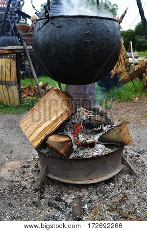 cooking in big pot on campfire outdoors