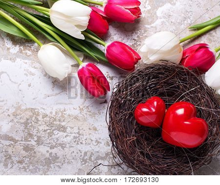 Red decorative hearts in nest and bright spring tulips flowers on grey textured background. Selective focus. Flat lay. Place for text. Toned image.