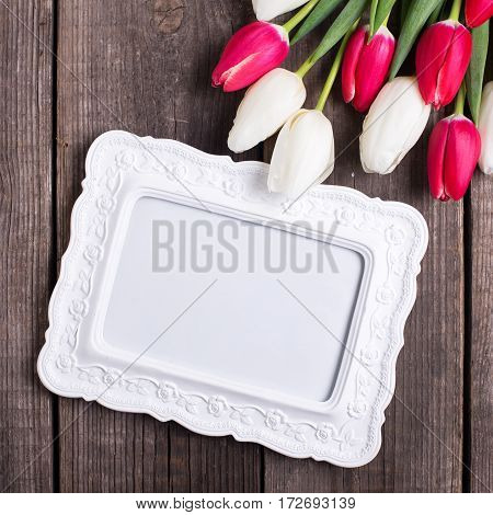 Empty frame and bright pink and white tulips flowers on rustic wooden background. Selective focus. Place for text. Flat lay. Square image.