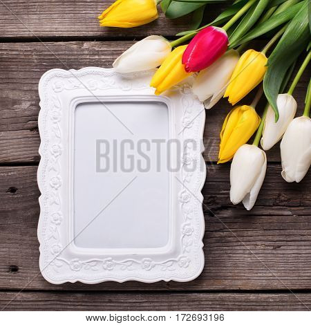 Empty frame bright yellow pink and white tulips flowers on retro wooden background. Selective focus. Place for text. Flat lay. Square image.