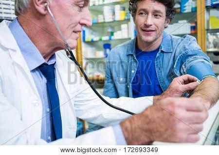 Pharmacist checking blood pressure of customer in pharmacy