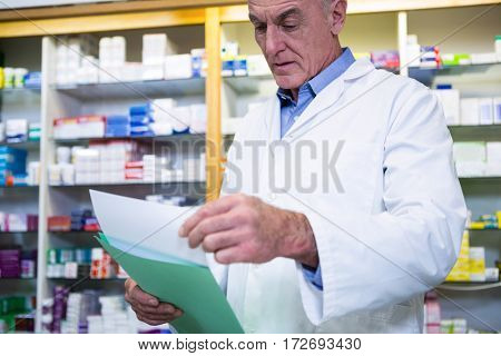 Pharmacist reading prescriptions in pharmacy