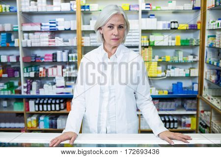 Portrait of pharmacist standing at counter in pharmacy