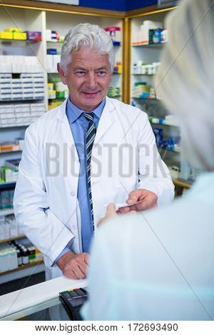 Pharmacist giving bill to customer in pharmacy