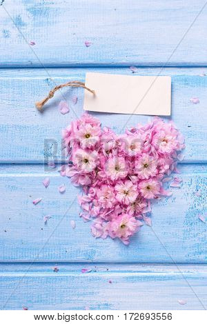 Heart from pink flowers and petals and empty tag on blue wooden planks. Selective focus. Place for text.
