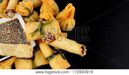 Group of mixed Oriental pastry wrapped snacks on a slate background