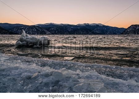 Beautiful winter landscape with a lake iceberg on the water and ice on the bank on the background of mountains at sunset