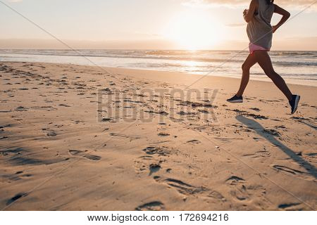 Outdoor shot of female exercising on the beach. Woman on morning run focus on feet.