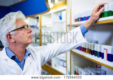 Pharmacist in lab coat checking medicines in pharmacy