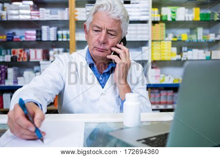 Pharmacist talking on mobile phone while writing prescriptions for medicines in pharmacy