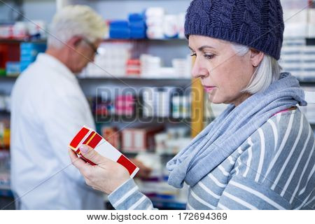 Customer checking a pill box in pharmacy