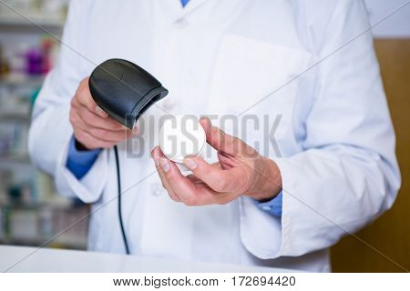 Pharmacist using barcode scanner on medicine container in pharmacy