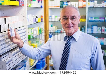 Portrait of pharmacist checking medicines in pharmacy