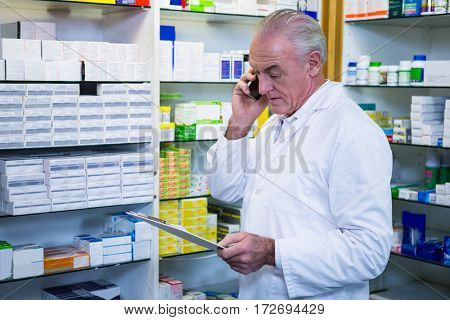 Pharmacist talking on mobile phone while checking medicines in pharmacy